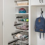 Entryway closet with racks pulled out for personal belongings