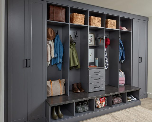 Closet showing coats on hooks with shoes and bags on shelves