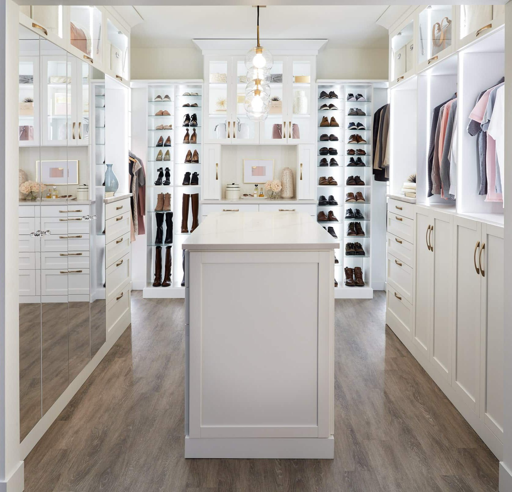 Custom white boutique closet with island and mirrors from Inspired Closets