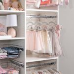 White little girls reach in closet with hanging rods for cloths in Las Vegas, NV