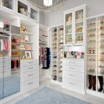 Custom boutique closet in houghton with shoe shrine shelving, built-in drawers and mirror doors