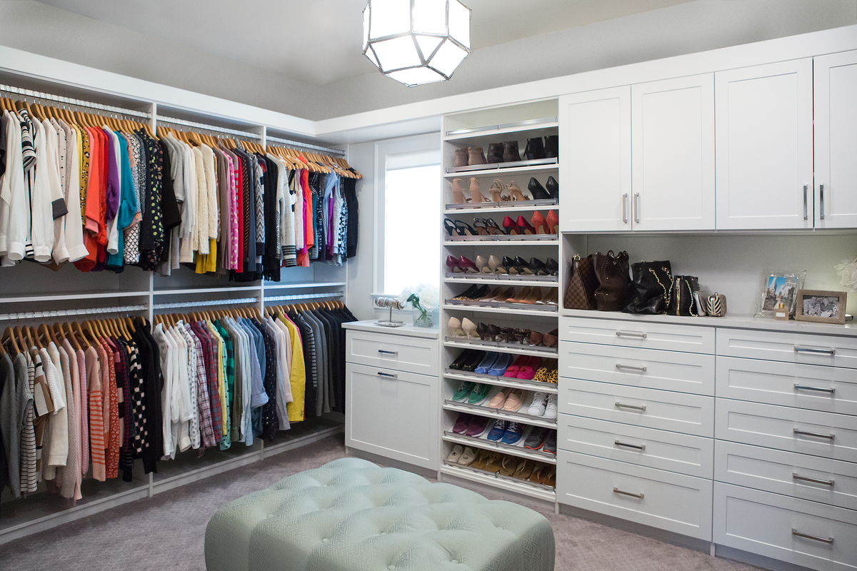 White boutique closet with shoe shelves, drawers and ottoman from Inspired Closets