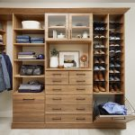 Walk in closet with storage for men's closet, custom shoe shrine shelves and pull out hamper.