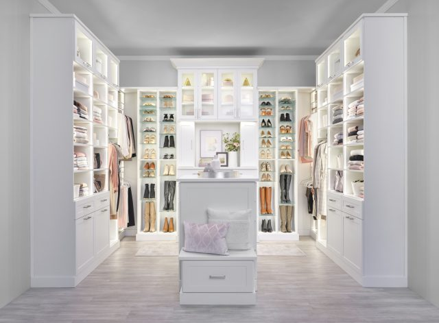 Custom lit boutique closet with island and adjustable shoe storage from Inspired Closets